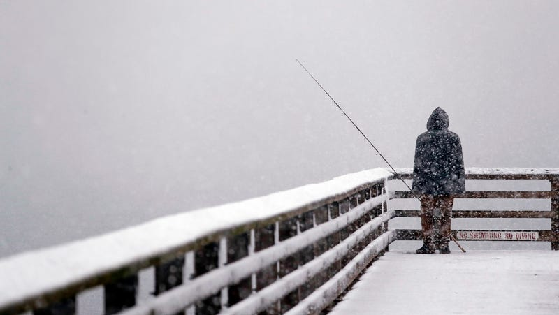 A person looks out toward the cityscape lost in a whiteout as he fishes from a pier during a snowstorm Friday, Feb. 8, 2019, in Seattle.