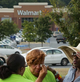 A woman who identified herself only as Tonya C. and says she was fired from Wal-Mart is comforted by friends during a demonstration outside a store, Sept. 5, 2013, in Hyattsville, Md.Chip Somodevilla/Getty Images