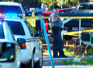 Police in Ladson, S.C., stand outside the home where they say a 13-year-old boy fatally shot an armed robber Nov. 10, 2015.WCSC-TV