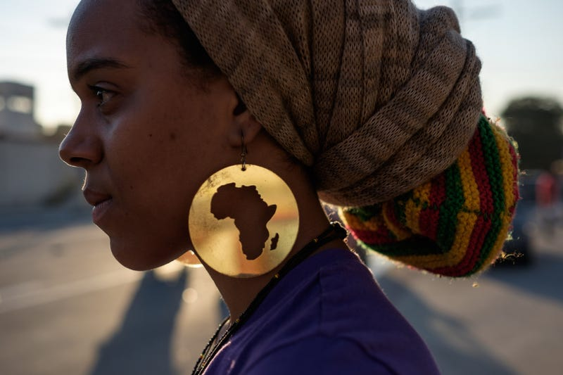 A protester wearing earrings with the image of the continent of Africa takes part in the International March Against the Genocide of Black People in Rio de Janeiro on Aug. 22, 2014. YASUYOSHI CHIBA/AFP/Getty Images