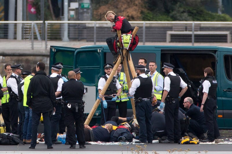 Emergency services surround protesters from the movement Black Lives Matter after they locked themselves to a tripod on the runway at London City Airport in London on Sept. 6, 2016. DANIEL LEAL-OLIVAS/AFP/Getty Images