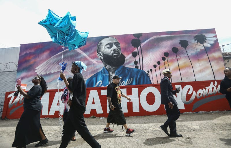 Fans walk as they wait outside The Marathon Clothing store for the funeral procession for slain rapper Nipsey Hussle on April 11, 2019 in Los Angeles, California.