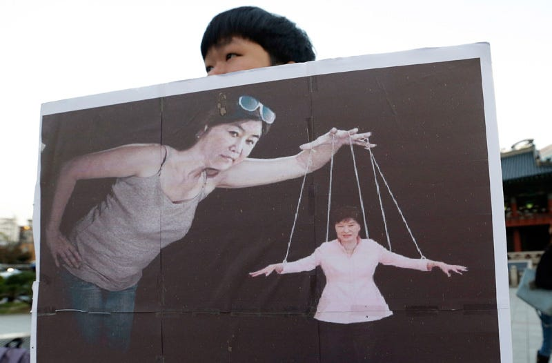 A South Korean college student holds a placard depicting South Korea's President Park Geun-hye as a marionette. Photo: AP