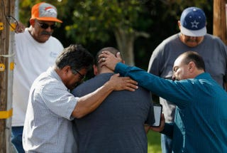A group of men embrace in prayer outside the crime scene where the suspects in the shooting at the Inland Resource Center were killed Dec. 3, 2015, in San Bernardino, Calif.Sean M. Haffey/Getty Images