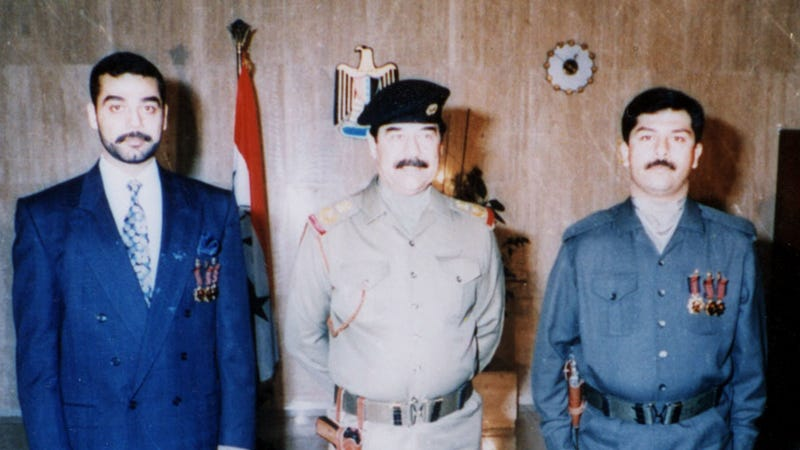 Uday (left) with his father, Saddam Hussein (center). Photo via Getty Images