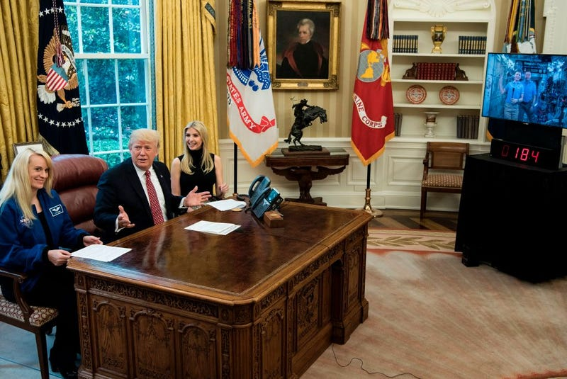 NASA astronaut Kathleen Rubins (eft) and Ivanka Trump sit with President Donald Trump after he spoke via video with NASA astronauts aboard the International Space Station from the Oval Office of the White House on April 24, 2017, in Washington, D.C.. (Brendan Smialowski/AFP/Getty Images)