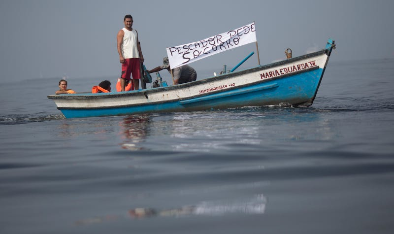 "Fishermen protest contamination in Guanabara Bay on July 3; ""Pescador pede socorro"" means ""fishermen ask for help."" Image via AP."