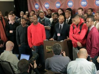 Surrounded by NBA players, Derek Fisher speaks to the media. (Seth Wenig/AP)