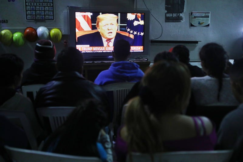 Migrants view a live televised speech by President Donald Trump on border security at a shelter for migrants on January 8, 2019 in Tijuana, Mexico. Tijuana continues to house migrants, many of whom are hoping to cross the border into the U.S.