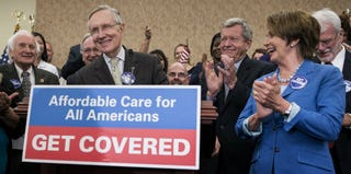 Senate Majority Leader Harry Reid and House Minority Leader Nancy Pelosi celebrate the ACA Oct 1. (Getty Images)