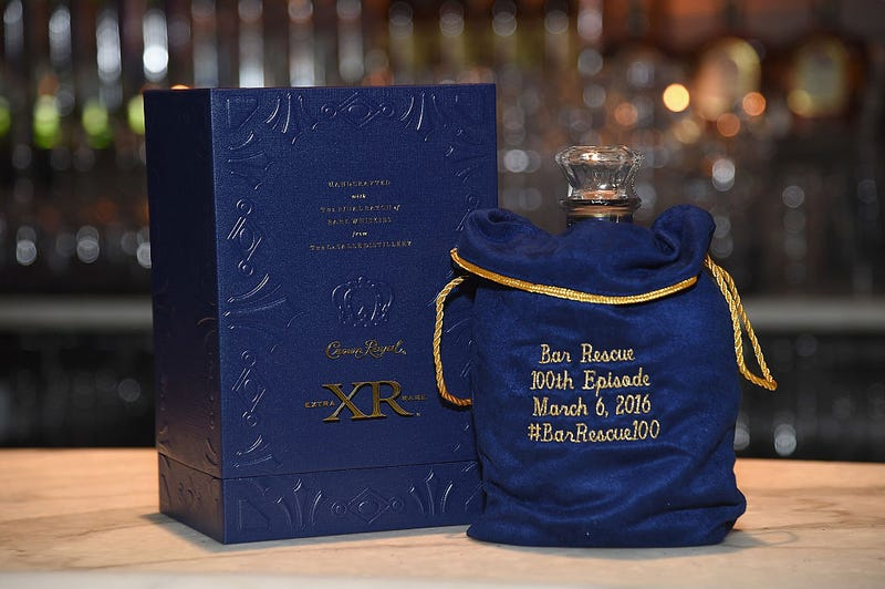 A bottle of Crown Royal with one of its custom embroidered bags