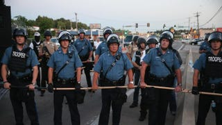 Police stand watch as demonstrators protest the shooting death of teenager Michael Brown Aug. 13, 2014, in Ferguson, Mo.Scott Olson/Getty Images
