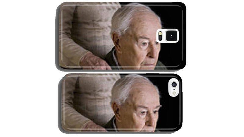 Anciano pensativo con la mano de su esposa sobre su hombro para el Samsung S5.  my-handy-design