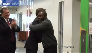 Ricky Jackson, right, hugs attorneys Friday after his release from Cuyahoga County Jail.Mail Online Screenshot