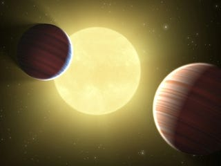 Illustration for article titled Two Saturn-sized planets are locked in elegant orbital dance around faraway star
