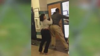 The teacher (left) involved in the incident is held back by a student. YouTube screenshot
