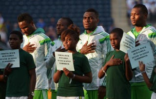 The player escorts for the Nigerian National Team hold signs in support of girls kidnapped earlier in Nigeria, before a game against Greece during an international friendly match at PPL Park on June 3, 2014, in Chester, Pa.Drew Hallowell/Getty Images