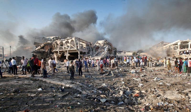 Somalis gather and search for survivors by destroyed buildings at the scene of a blast in the capital Mogadishu in Somalia on Oct. 14, 2017.  (Farah Abdi Warsameh/AP Photo)