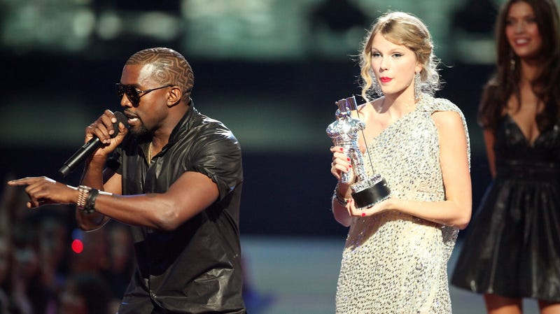 "Kanye West (L) jumps onstage after Taylor Swift (C) won the ""Best Female Video"" award during the 2009 MTV Video Music Awards on September 13, 2009, in New York City."