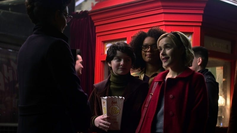 Surrounded by her friends, Sabrina (Kiernan Shipka) chats with someone who looks to be Michelle Gomez's Mary Wardwell.