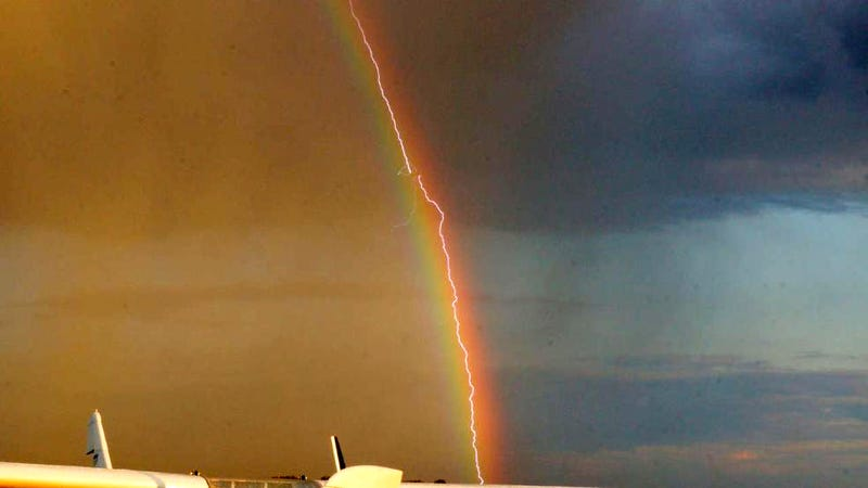 Illustration for article titled Amazing photo shows lightning striking an airliner flying in a rainbow