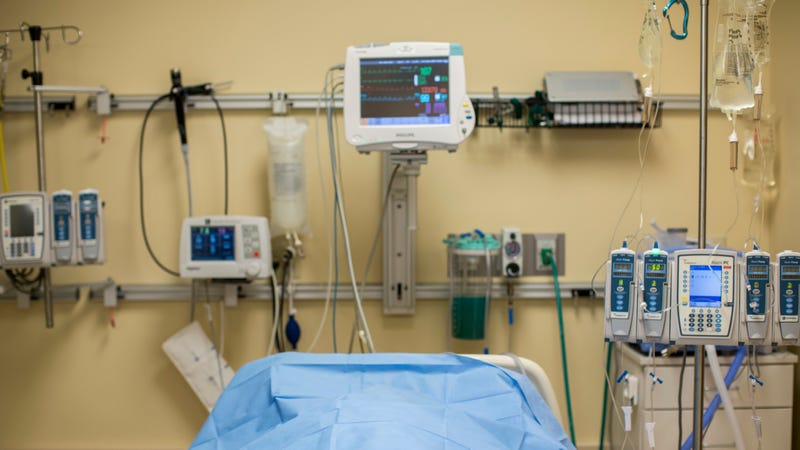 The body of a brain-dead potential organ donor lies covered on a bed at Mid-America Transplant Services in St. Louis.