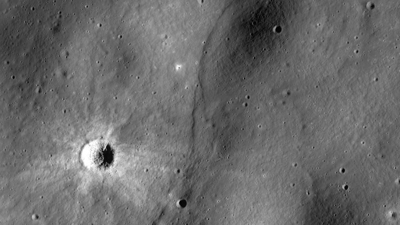 A lobate scarp, a potential lunar fault line, bisects this image.