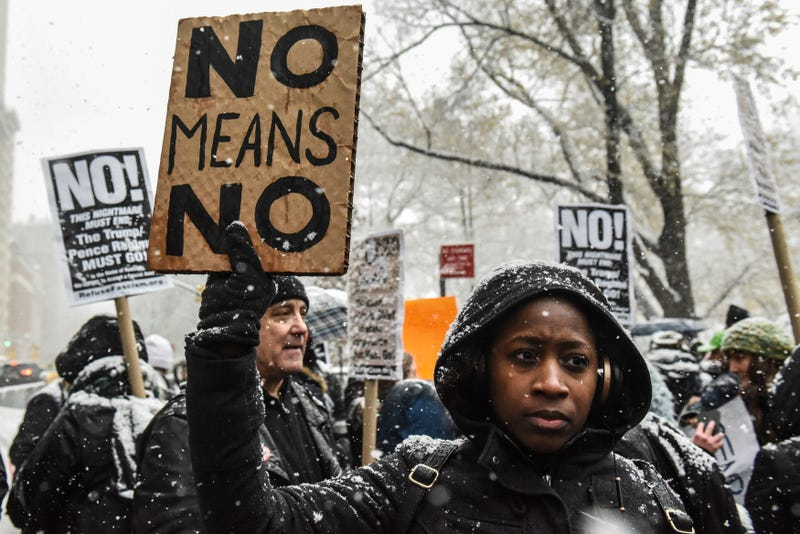 People carry signs addressing the issue of sexual harassment at a #MeToo rally outside Trump International Hotel  in New York City on Dec. 9, 2017. (Stephanie Keith/Getty Images)