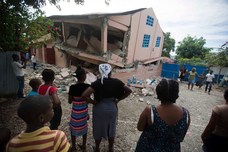 Residents stand looking at a collapsed school damaged bya magnitude 5.9 earthquake the night before, in Gros Morne, Haiti, Sunday, Oct. 7, 2018. Emergency teams worked to provide relief in Haiti on Sunday after the quake killed at least 11 people and left dozens injured.
