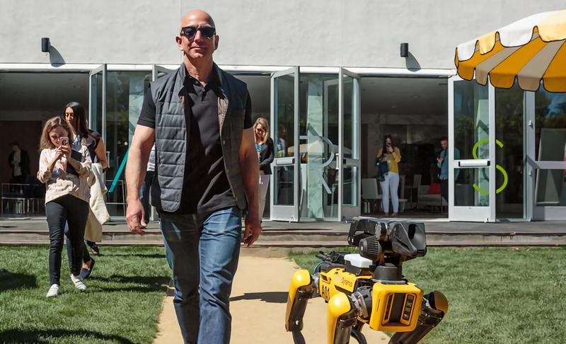 Bezos caminando junto a uno de los robots de Boston Dynamics.