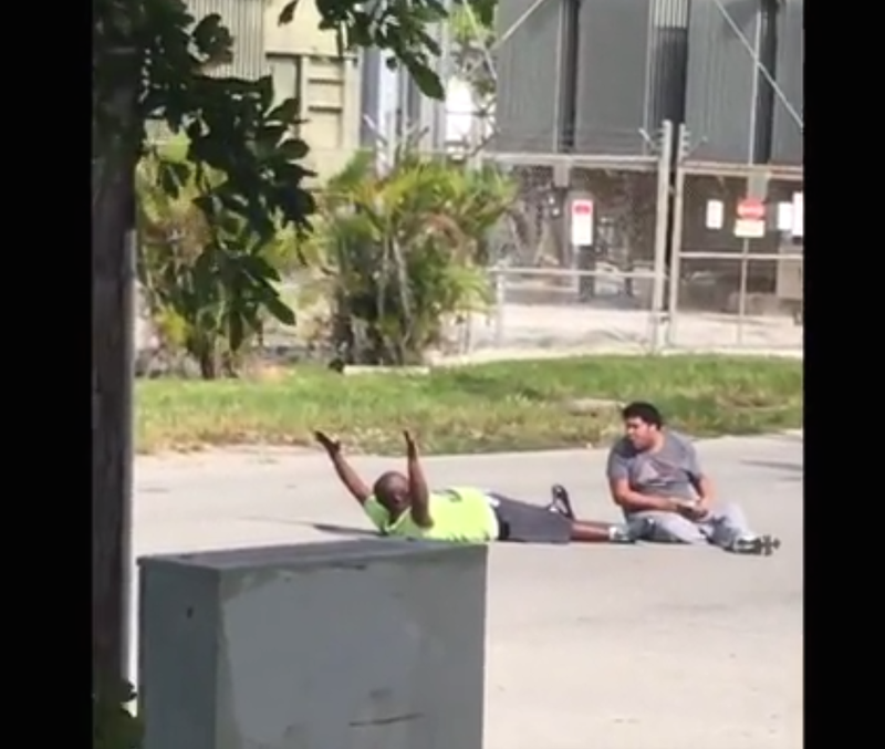 Charles Kinsey lies in a North Miami, Fla., street with his hands up as he tries to reason with his autistic patient and with police before an officer shoots him July 18, 2016.WSVN screenshot