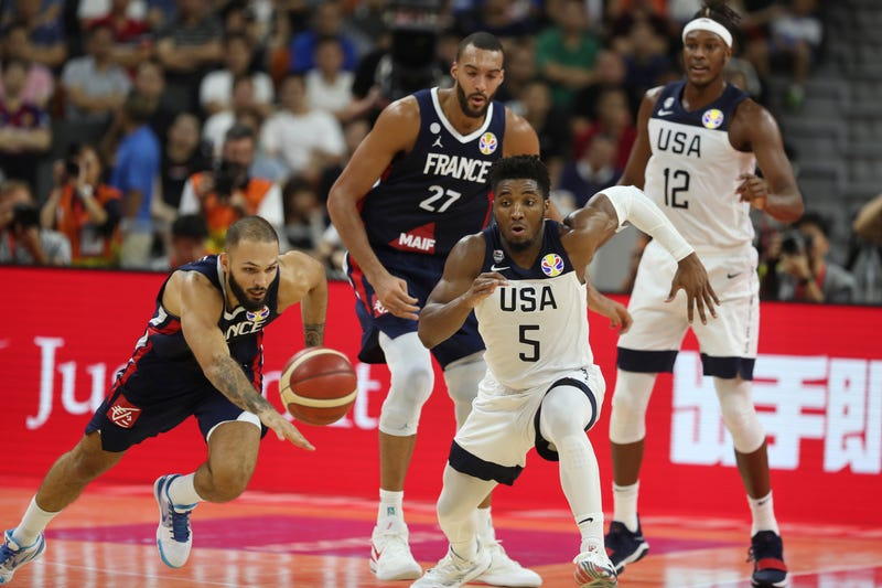 United States' Donovan Mitchell, center and France's Evan Fournier at left races for the ball during a quarterfinal match for the FIBA Basketball World Cup in Dongguan in southern China's Guangdong province on Wednesday, Sept. 11, 2019. France defeated United States 89-79.