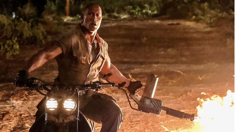 Illustration for article titled Here's a Photo of the Rock Wielding a Flamethrower While Riding a Motorcycle on the Jumanji Set