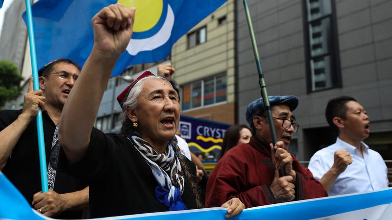 Rebiya Kadeer, president of the World Uyghur Congress (WUC) and people chant slogans and wave flags during a protest march on June 29, 2019 in Osaka, Japan.