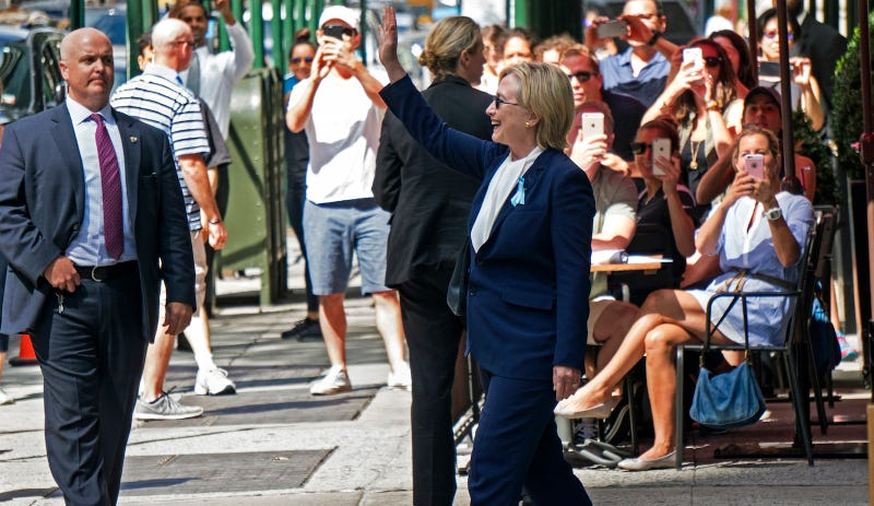 Hillary Clinton greets onlookers outside her daughter's apartment building after becoming unwell at Sunday's 9/11 anniversary ceremony. Image via Associated Press.