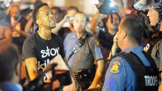 A protester speaks emotionally with a police officer during a protest in Ferguson, Mo., on Aug. 19, 2014. Michael B. Thomas/AFP/Getty Images