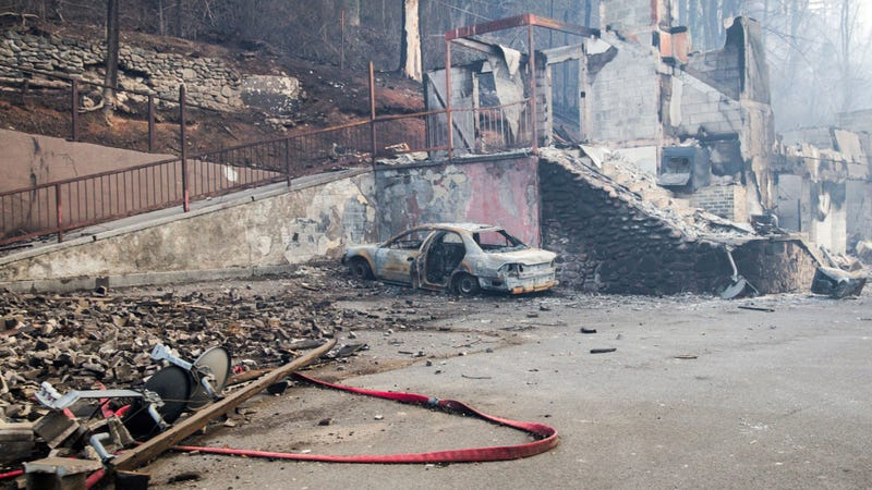 A scorched vehicle sits next to a burned out building in Gatlinburg, Tennessee. (Image: AP)