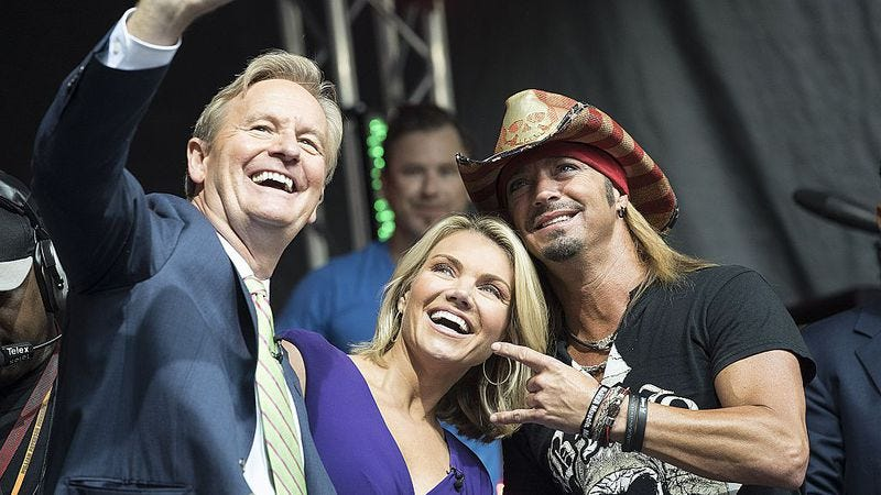 Nauert (center) poses for selfies with co-host Steve Doocy and Bret Michaels. (Debra L Rothenberg / Getty Images)