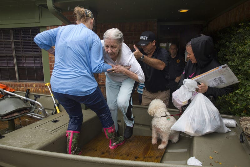 An elderly woman leaves her home and is helped into a boat after flooding caused by heavy rain during Hurricane Harvey August 29, 2017 in the Bear Creek neighborhood in west Houston, Texas (Photo by Erich Schlegel/Getty Images)