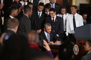 Surrounded by students from Chicago's Youth Guidance program Becoming a Man, President Barack Obama signs an executive memorandum related to his My Brother's Keeper initiative in the East Room of the White House Feb. 27, 2014, in Washington, D.C.Chip Somodevilla/Getty Images