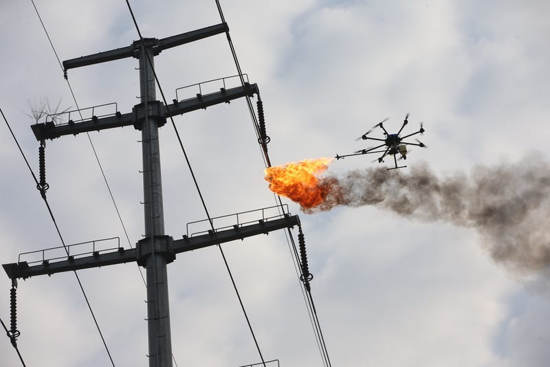 Electric company maintenance workers in Xiangyang, China used a fire-shooting drone to burn garbage from electrical wires (Photo by Wang Hu/VCG)