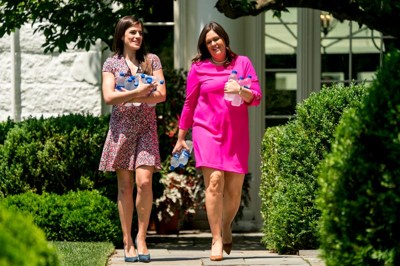 In this photo taken Friday, June 1, 2018, President Donald Trump's personal secretary Madeleine Westerhout, left, and White House press secretary Sarah Huckabee Sanders, right, carry bottles.