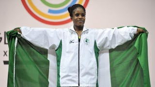 Nigeria's gold medalist Chika Amalaha celebrates on the podium at the medal ceremony for the women's weightlifting 117-pound class during the 2014 Commonwealth Games in Glasgow, Scotland, July 25, 2014.Andy Buchanan/AFP/Getty Images