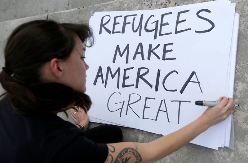 Photo of protester preparing a sign for a rally against President Donald Trump's executive order on Muslim immigration in Miami via AP.