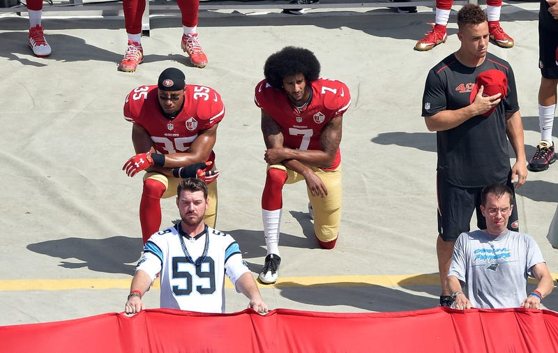 Colin Kaepernick, No. 7, and Eric Reid, No. 35, of the San Francisco 49ers kneel during the national anthem before their game against the Carolina Panthers at Bank of America Stadium on Sept. 18, 2016, in Charlotte, N.C.Grant Halverson/Getty Images