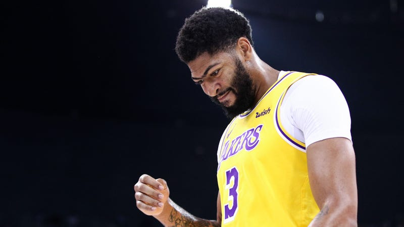 Pictured: Los Angeles Lakers star Anthony Davis looking down at the roof of a two-story building, just out of frame