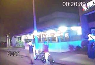 Screenshot of police dash-cam footage showing Ricardo Diaz-Zeferino with his hands on his headAP