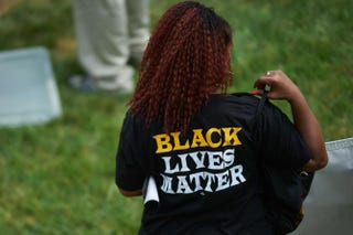 "A woman wearing a shirt with ""Black Lives Matter"" on Aug. 9, 2015, at the Canfield Apartments in Ferguson, Mo., during a memorial service for Michael Brown Jr.Michael B. Thomas/AFP/Getty Images"