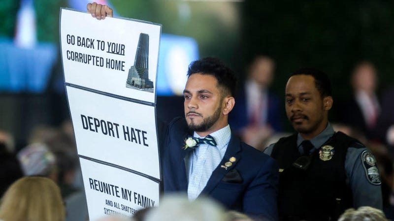 Virginia state Del. Ibraheem Samirah holds up a sign as Donald Trump delivers remarks during the 400th anniversary celebration of the first representative legislative assembly at Jamestown on July 30, 2019, in Jamestown, Va.