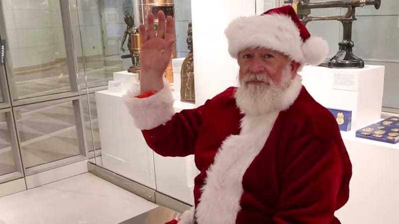 Santa Claus raises his hand as he awaits his biometric scan for entry into the United States (US Customs and Border Protection screenshot via YouTube)